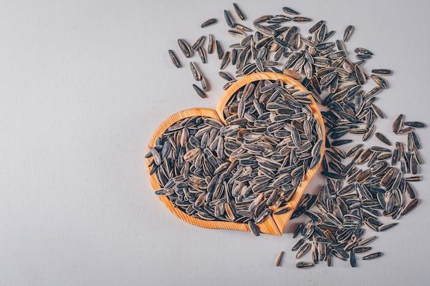 Черные семена подсолнуха на доске в форме сердца и белом фоне, вид сверху.