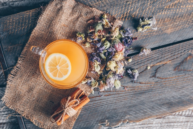 トップビューオレンジ色のカップの袋に布と暗い背景の木にレモンと紅茶の種類の水。横型