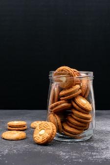 暗い表面のガラス瓶の中のクッキー