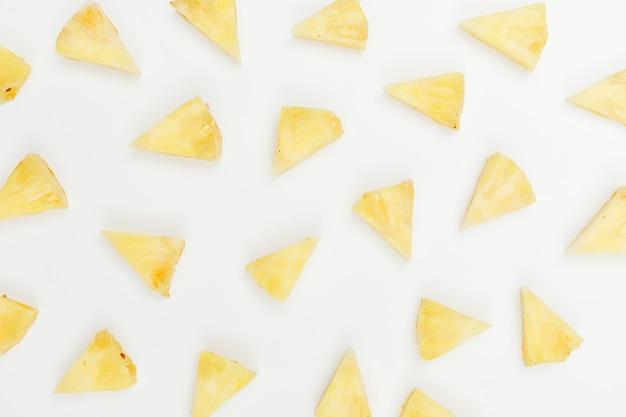 Кусочки нарезанного ананасового треугольника на белом. плоская планировка