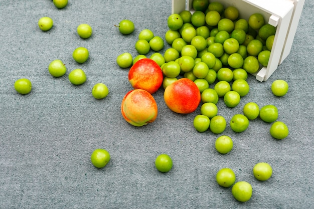 グレーのハイアングルで白い長方形のボウルにおいしい桃と散りばめられた緑の梅。