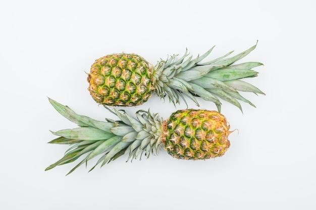 Два свежих ананаса вид сверху на белом