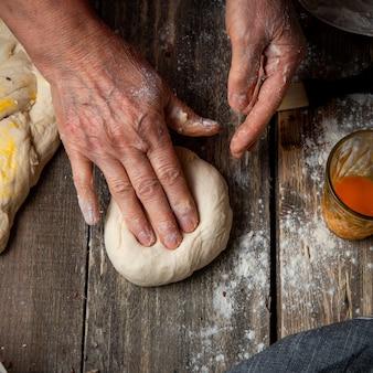 Самка замешивая тесто руками
