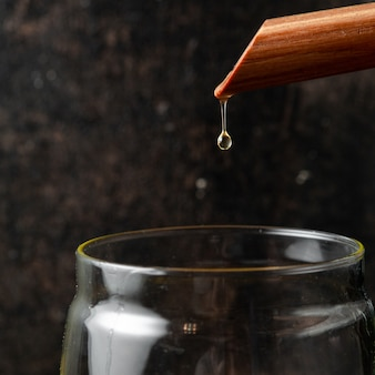 ガラスの瓶のクローズアップに油を注ぐ