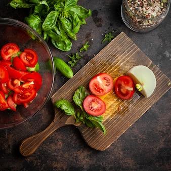 スライスした野菜をトマト、ガラスのボウルに穀物の瓶とキュウリ、玉ねぎとほうれん草の暗いとまな板の上から見る