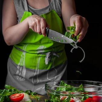 スライスした玉ねぎとほうれん草を季節のサラダ側面に追加する女性