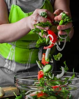 Женщина, добавляя овощи в сезонный салат вид сбоку