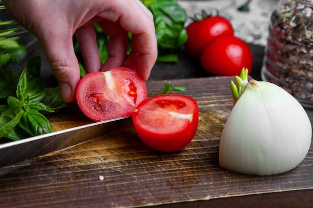 木の板のクローズアップの女性切削トマト。