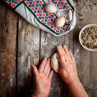 木製のテーブルトップビューに手で生地を形作る女性