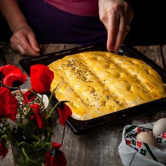 Женщина брызгая специю на тесто перед печь взгляд высокого угла.