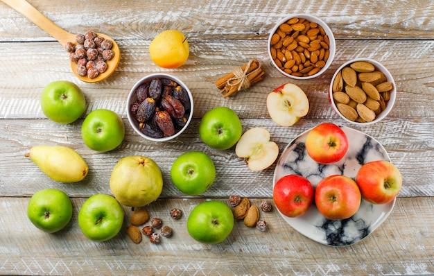 Яблоки и ломтики в тарелке с грушей, палочки корицы, очищенный и неочищенный миндаль в мисках, орехи в деревянной ложке, вид сверху на деревянный