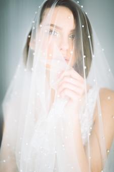 Красивая женщина, стоя и глядя в свадебное платье в комнате