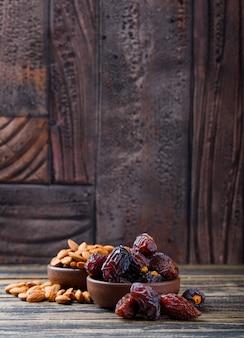 Финики и миндаль в глиняных табличках на фоне деревянных и каменных плиток. вид сбоку.