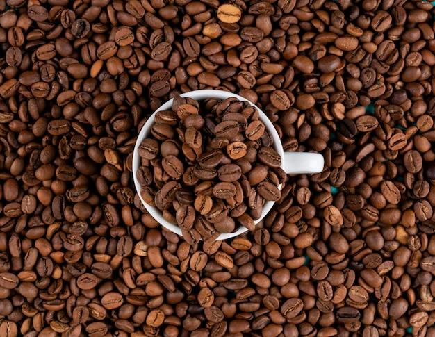 カップの表面を持つトップビューコーヒー豆