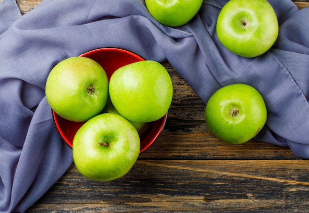 Зеленые яблоки в шаре на предпосылке деревянных и ткани, плоском положении.