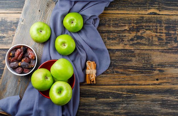 Зеленые яблоки с палочками корицы, миска даты на деревянной части в миске на деревянном и текстильном фоне