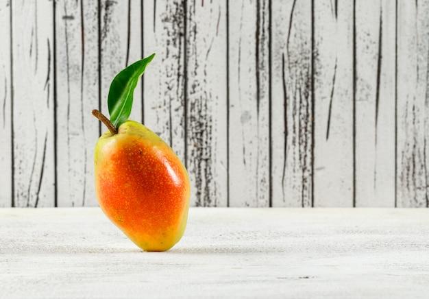 汚れた木製と白の背景に葉と梨
