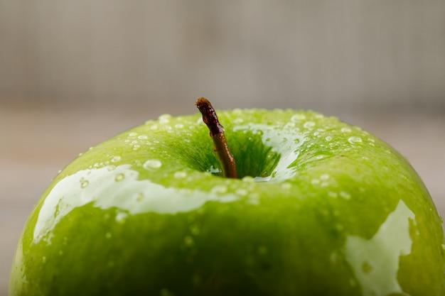 汚れた背景に酸っぱい青リンゴ。閉じる。