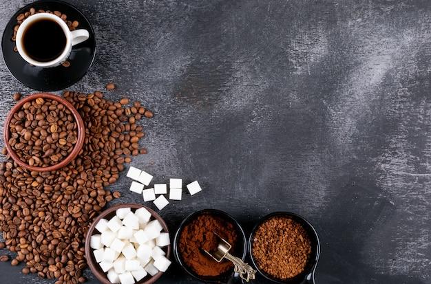 コーヒー豆と暗いテーブルの上の砂糖キューブトップビューコーヒーカップ