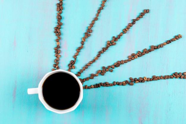 青いテーブルの上のコーヒー豆光線とトップビューコーヒーカップ