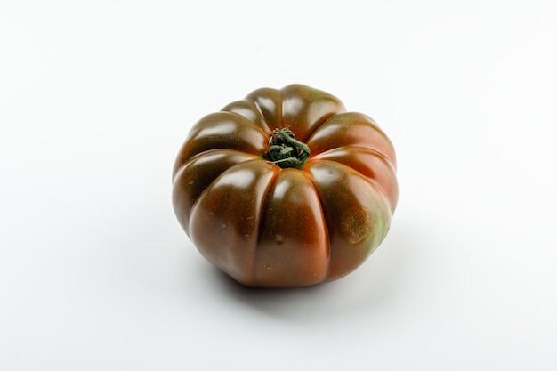 白い壁に新鮮な黒いトマト。 。