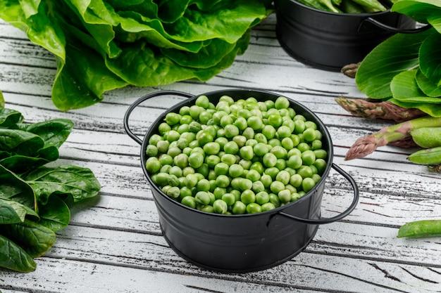 エンドウ豆、アスパラ、スイバ、チンゲン菜、レタス、グリーンポッドの鍋、木製の壁、高角度のビュー。