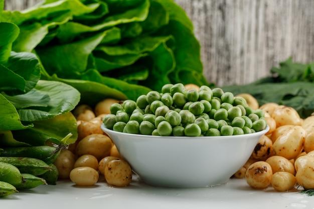 Горох с зелеными стручками, шпинатом, щавелем, салатом в миску на белой и шероховатой стене, вид сбоку.