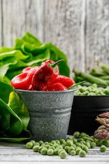 Горох и перец с листьями салата, зеленые стручки, спаржа, бок чой в ведра на шероховатой деревянной стене, вид сбоку.