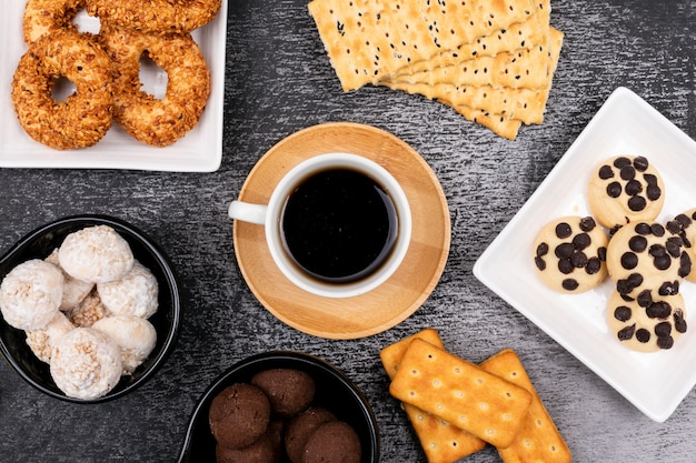 Кофейная чашка с разными печеньями на темном столе