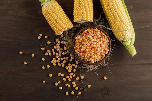 Кукурузные зерна в глиняной тарелке с початками сверху на деревянном столе