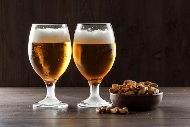 Пенное пиво с фисташкой в бокалах на деревянном столе, вид сбоку.