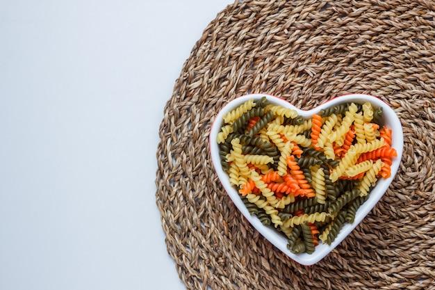 Макароны фузилли в миску в форме сердца на белом и плетеном столе столовых. вид сверху.