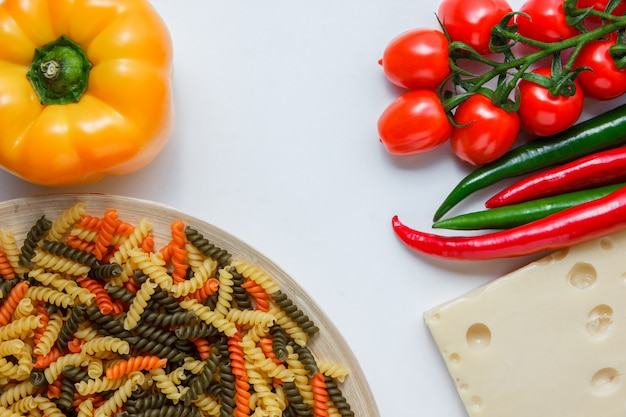 Паста фузилли в тарелку с помидорами, перцем, сыром высокий угол зрения на белом столе