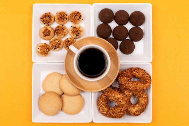 正方形のプレートと黄色の表面にコーヒーカップのトップビューの異なるクッキー