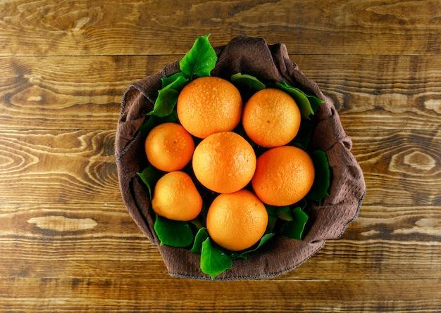 Цитрусовые с листьями на деревянном и кухонном полотенце, вид сверху.