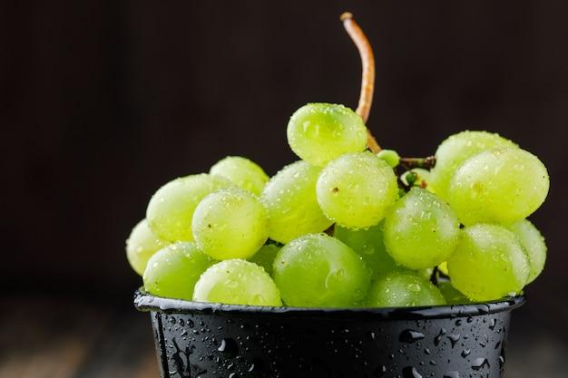Виноградная гроздь в черном ведре на деревянной поверхности, крупный план.
