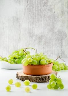 Виноградные гроздья в тарелках с деревянным куском на белой поверхности