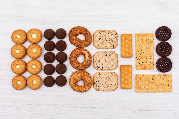 白い表面にトップビューの異なるクッキー