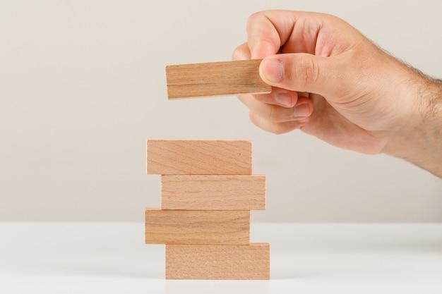 白い背景の側面図の事業計画のコンセプト。タワーに木製のブロックを配置する手。
