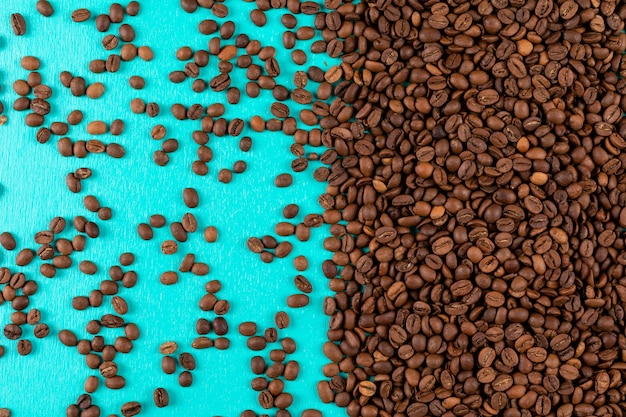 Вид сверху кофейных зерен на синей поверхности