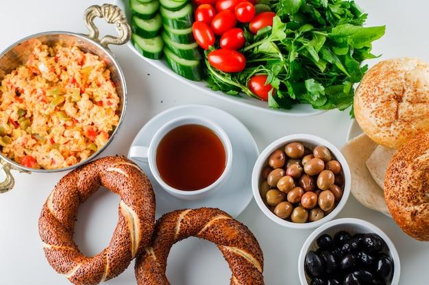Вкусная еда в горшочке с чашкой чая, турецким бубликом, салат сверху на белой поверхности