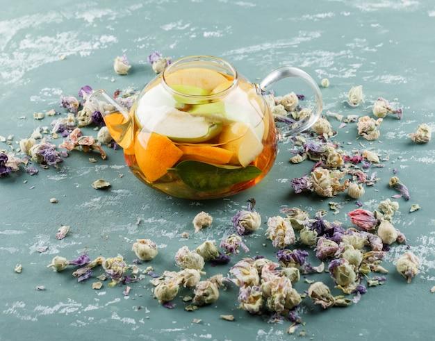 フルーツを注いだ水と石膏の表面のティーポットにドライフラワー