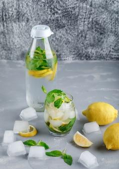 Ледяная детокс-вода с лимонами, мятой в стакане и бутылкой на серой и шероховатой поверхности