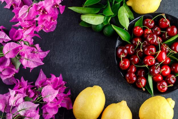 Лимоны с листьями, цветами, вишней на серой поверхности