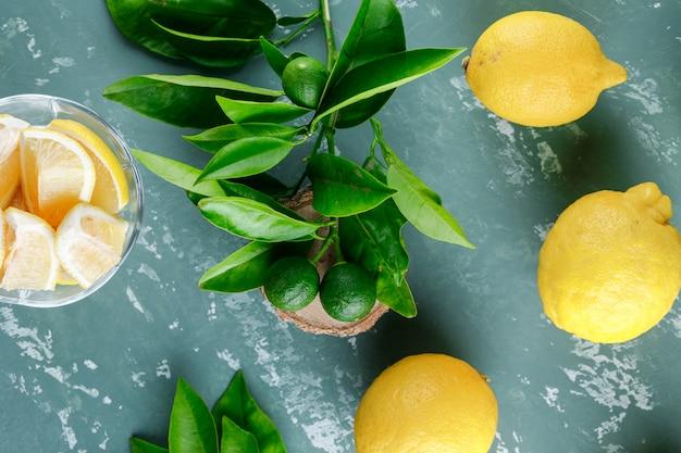 Лимоны с листьями, деревянная доска на гипсовой поверхности, вид сверху
