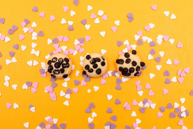 Печенье сверху с кусочками шоколада с украшениями в форме сердца на желтой поверхности