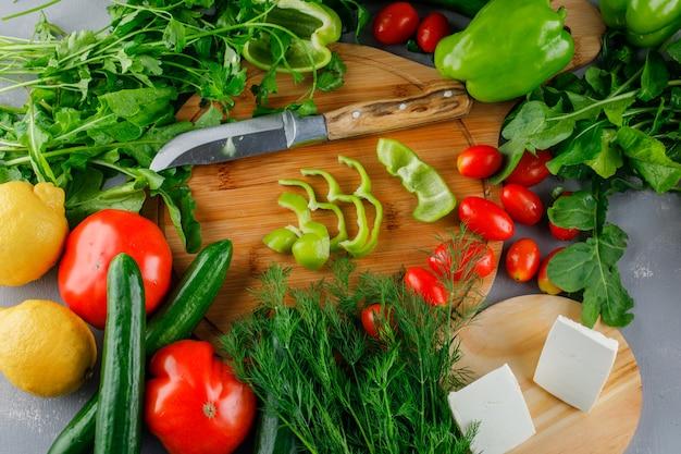 灰色の表面にまな板の上のトマト、塩、チーズ、レモン、野菜、ナイフでピーマンをスライス