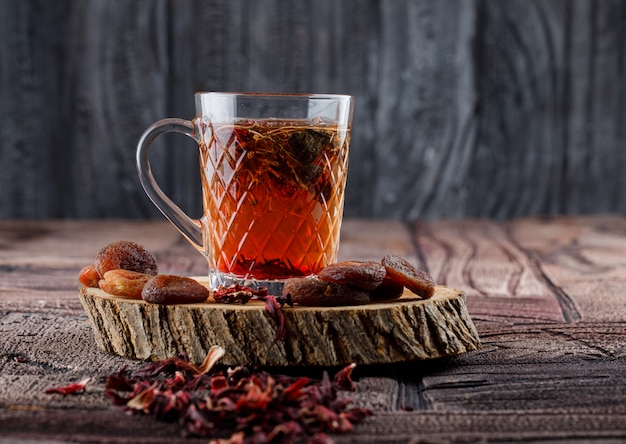ドライフルーツと花、石のタイルと木製の表面のカップに木のレモン