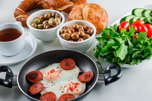 Высокий угол обзора вкусные блюда в горшочке с чашкой чая, турецкий бублик, помидоры, зелень на белой поверхности