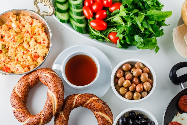 Набор из чашки чая, турецкого бублика, салата и вкусной еды в горшочке на белой поверхности